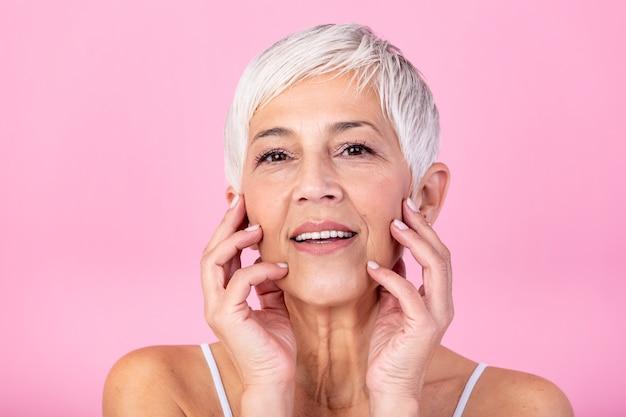 彼女の完璧な肌に触れるとカメラ目線の美しい年配の女性の肖像画。ピンクの背景に分離された顔をマッサージしわと成熟した女性の顔をクローズアップ。老化プロセスの概念。