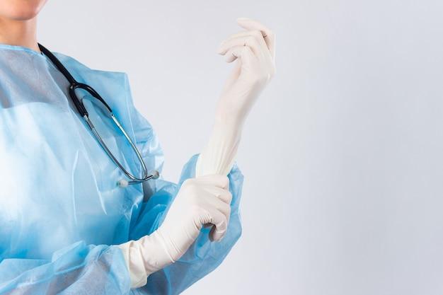 女性医師の外科医が手術の準備をして、彼女は手袋とスクラブ、ヘルスケア、準備の概念を着ています。クリニックでゴム手袋を置く若い医者をクローズアップ