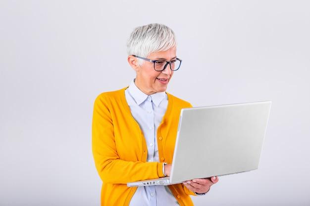 ラップトップコンピューターを使用して灰色の背景の上に孤立して立っている陽気な熟女のイメージ。ラップトップコンピューターを保持している笑顔のシニア女性の肖像画