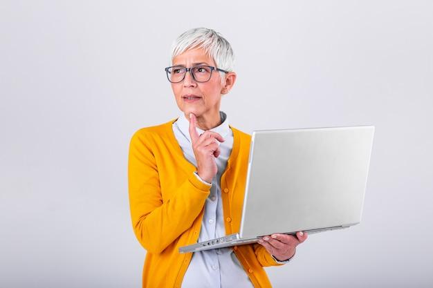 ラップトップコンピューターを保持している灰色の背景に分離された思考成熟したビジネス女性の写真。ラップトップコンピューターを使用して混乱している年配の女性のイメージ。手で顔を押しながらノートパソコンを見ています。