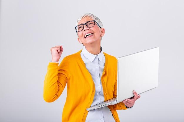 Портрет жизнерадостной зрелой женщины с портативным компьютером и праздновать успех изолированный над серой предпосылкой.