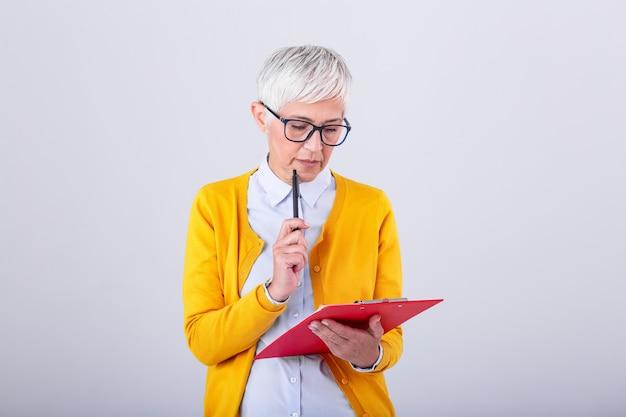 Фото думая зрелой бизнес-леди изолированной над серой стеной держа доску сзажимом для бумаги и ручку. изображение путать старшие женщины, глядя на документы