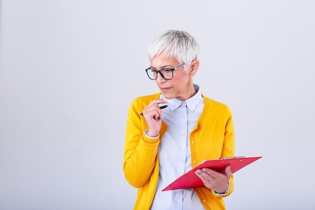 Зрелая коммерсантка в официально носке думая о предложении о работе перед подписанием документов. бизнес женщина, держащая буфера обмена. современная трудолюбивая женщина держит в руках доску с клипсой