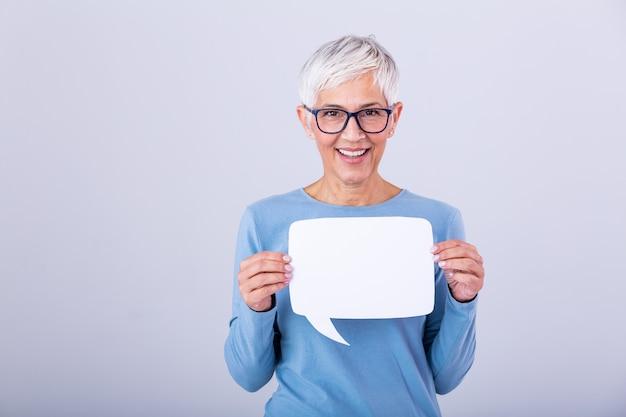 Красивая зрелая женщина в очках, держа речи пузырь своими руками и улыбается