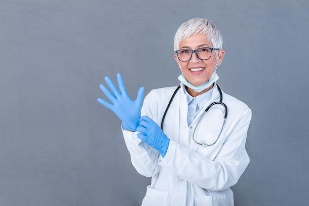 Старший женский доктор надевая защитные перчатки, изолированные на стене. доктор надевает стерильные перчатки