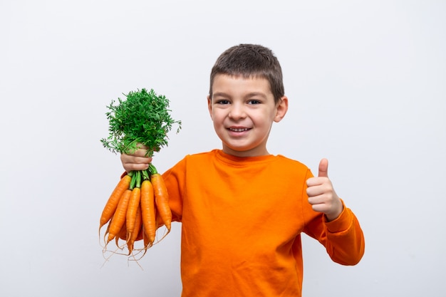 Прелестный маленький ребенок с морковью. здоровые органические овощи для детей. маленький малыш мальчик держит в руках морковь.