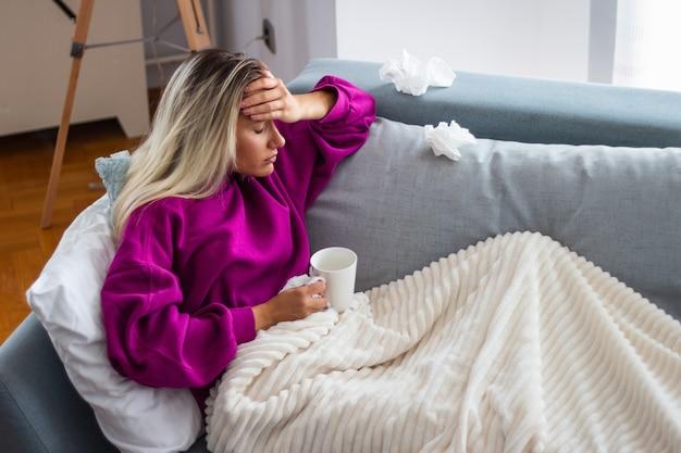 毛布の下に座って頭痛で病気の女性。季節性感染症、インフルエンザ、ベッドに横たわっているアレルギーを持つ病気の女性。病気の女性は、高熱とインフルエンザで休んでいるベッドに横たわっている毛布で覆われています。