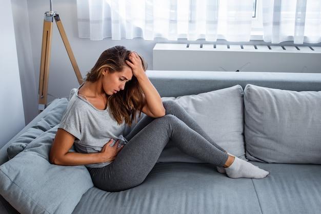 Взгляд молодой женщины страдая от боли в животе на софе дома. женщина сидит на кровати и болит живот. молодая женщина страдает от боли в животе, сидя на диване у себя дома