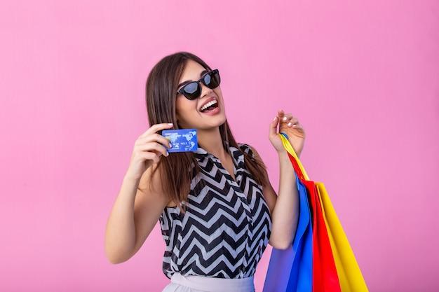 ファッショナブルな身に着けている美しい女の子と買い物袋とクレジットカードを保持しているサングラス