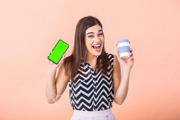 Молодая самка держит смартфон и чашку кофе