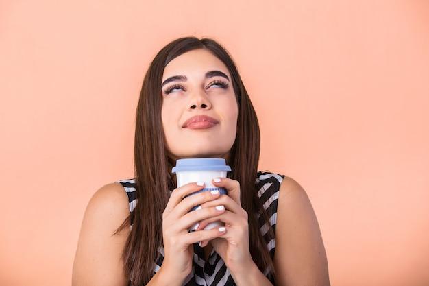 寄り添う手で暖かいラテのカップを保持している若い女性