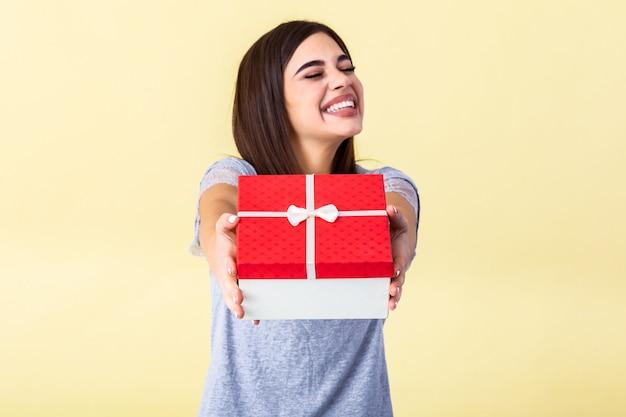 Молодая женщина держит в руках красную подарочную коробку