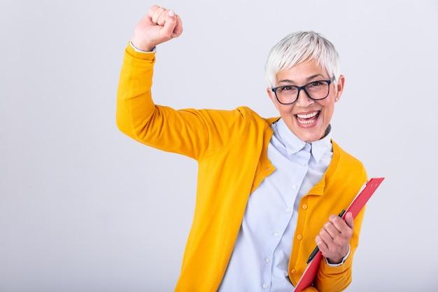 クリップボードとドキュメントを手に持つシニアビジネス女性
