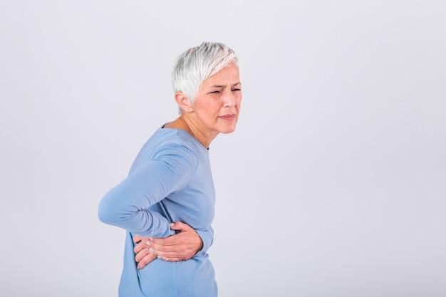 Пожилая женщина с седыми волосами, касаясь ее больное бедро.