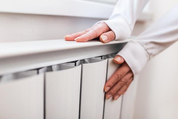 頑丈なラジエーター-セントラルヒーティング。女性は家の中央暖房システムで彼女の手を暖かくしています