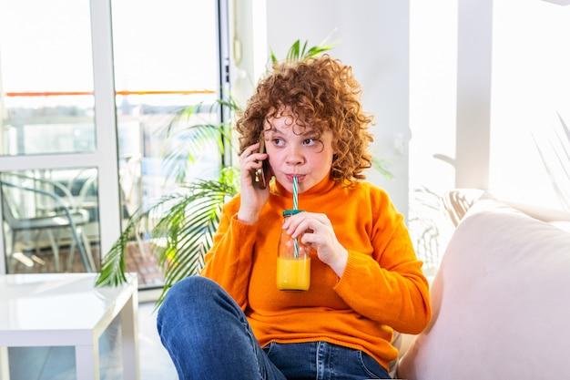 自宅の電話で話している幸せな陽気な若い女性、ソファーに座って携帯電話で電話に答える笑顔の十代の少女、携帯電話で話しているとオレンジジュースを飲んで楽しい面白い会話