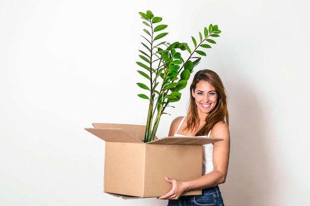 Молодая счастливая женщина переезжает в новый дом. она приносит коробку со своим любимым растением в свой новый дом.
