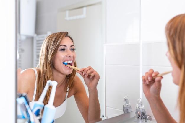 バスルームで歯を磨くと鏡で鏡を見て魅力的な女性の肖像画。健康な歯。鏡を見て、バスルームで歯を磨く幸せな素敵な若い女性