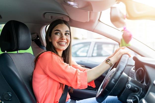 かわいい若い女性が車を運転して幸せ。車を運転して笑顔の美しい若い女性の画像。安全ベルトが付いている幸せな女性ドライバーステアリング車の肖像画