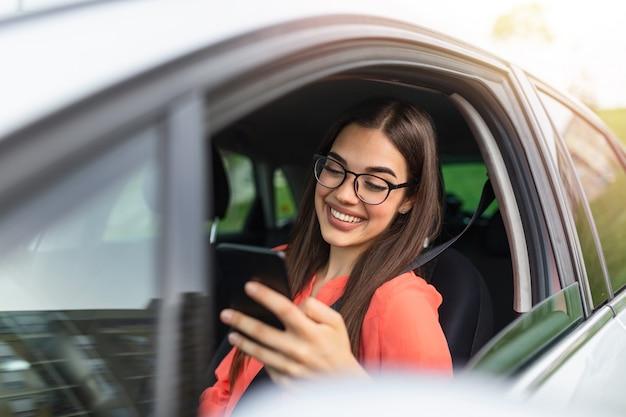 Красивая бизнес-леди использует умный телефон и усмехается пока сидящ на переднем сиденье в автомобиле. портрет красивой улыбающейся счастливой женщины в автомобиле.
