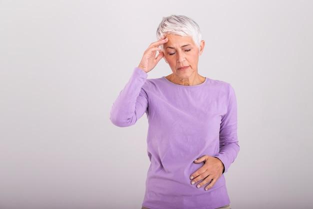 頭痛を抱え、気分が悪い中、両手で頭を抱えている熟女。頭痛、痛みの表情を持つ年配の女性。頭痛片頭痛を持つ高齢者の女性