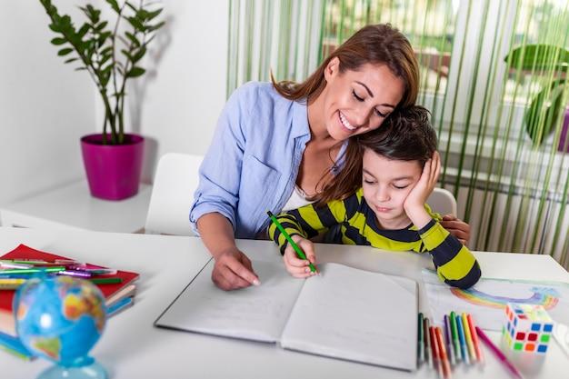 小さな男の子が宿題をするのを助けるお母さん。母と息子が一緒に描いている、ママが宿題を手伝っています。