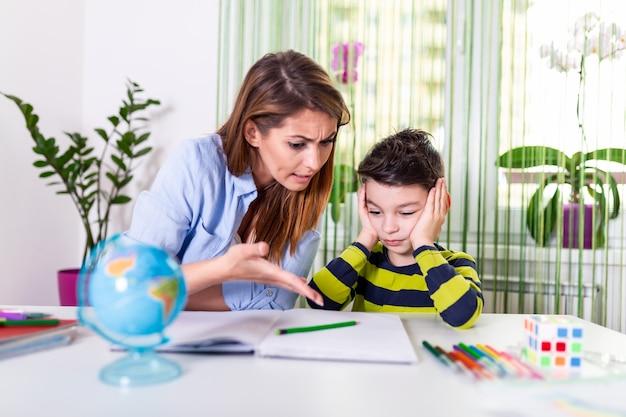 Усиленная мать и сын расстроенные над домашней работой отказа, концепцией проблем школы.