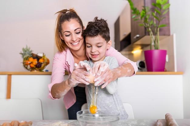 Молодая мама и милый маленький сын мальчик готовит тесто, печет печенье и развлекается на кухне