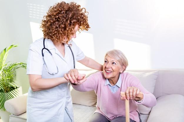 年配の女性がリビングルームのソファから起き上がるのを助ける女性介護者。起床する年配の女性を支援する笑顔の看護師。