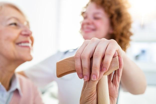 年配の女性の手に触れる人のクローズアップ。特別養護老人ホームで若い介護者の手を握る高齢者の女性の手。
