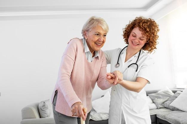幸せな女性介護者と自宅で一緒に歩いている年配の女性の肖像画。高齢者の女性の世話をする専門の介護者。