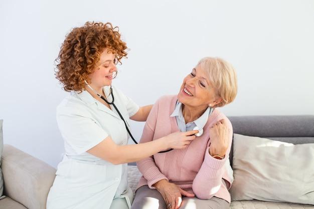 若い女性医師が上級の患者を調べます。年配の女性を調べる白いコートを着ている若い女性医師。