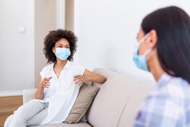 Две лучшие подруги женского пола, сидящие на расстоянии друг от друга, надевают маску и разговаривают на диване, предотвращая распространение коронавирусной инфекции.