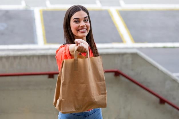 Улыбается молодая женщина, глядя на камеру, держа эко мешок доставки продуктов питания доставки социального пожертвования