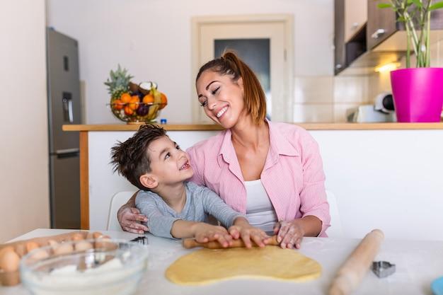 Счастливая любящая семья готовит пекарню вместе. мать и ребенок сын мальчик готовить печенье и веселиться на кухне.