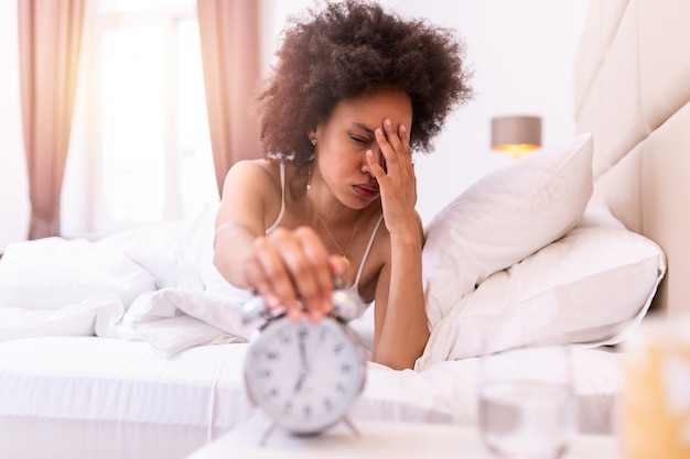 Молодая негритянка просыпается с головной болью, грустна, мигрень подчеркнута, плачет, разочарован ощущением по утрам. сонная молодая женщина, протягивая руку к звон будильник, чтобы выключить его.