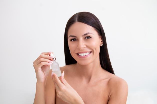 ピペットで顔に美容液を適用する美少女。