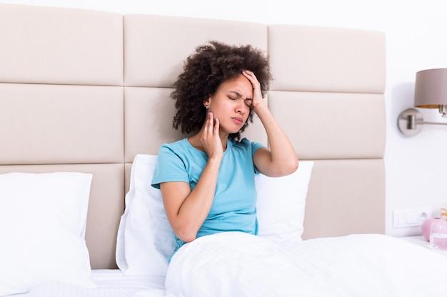 Портрет привлекательная женщина, сидя на диване у себя дома с головной болью, чувство боли и с выражением нездоровья.
