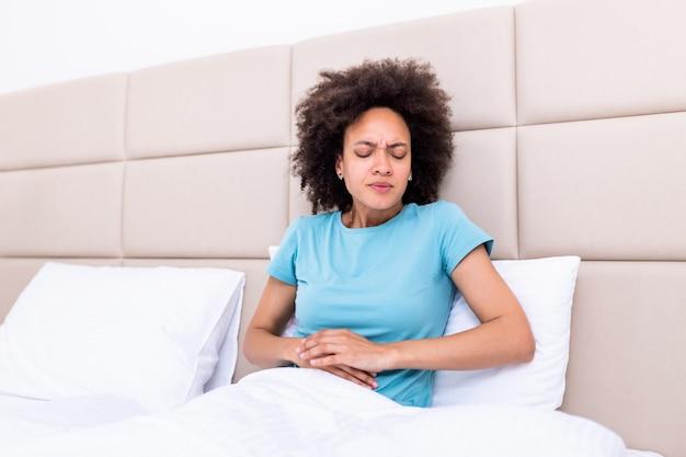 自宅のベッドに悲しい横たわっている月経痛に苦しんでいる腹に対して手を繋いでいる痛みを伴う表情の女性