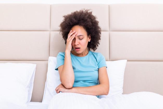 Подавленная черная молодая женщина сидит на диване расстроен, имея личные проблемы