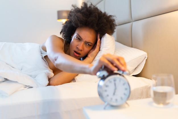 Разочарованный женщина закрыла уши от будильника утром. портрет раздражен молодой женщины, охватывающих уши из-за звон будильника утром, лежа в