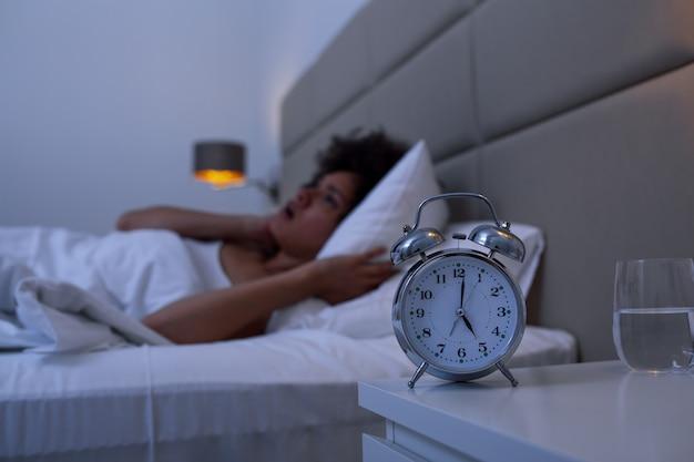 目を開けてベッドに横たわっている不眠症の女性。不眠症と夜に彼の問題を考えて睡眠障害に苦しんでいるベッドの中で女の子