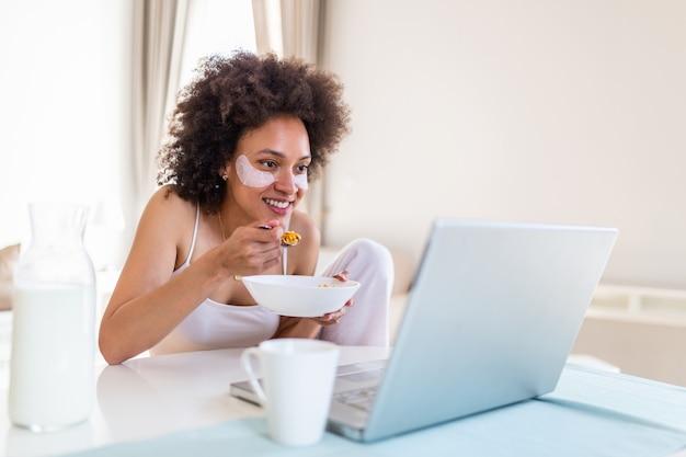 ラップトップを使用してテーブルに朝座っている魅力的な若いアフリカ系アメリカ人女性。