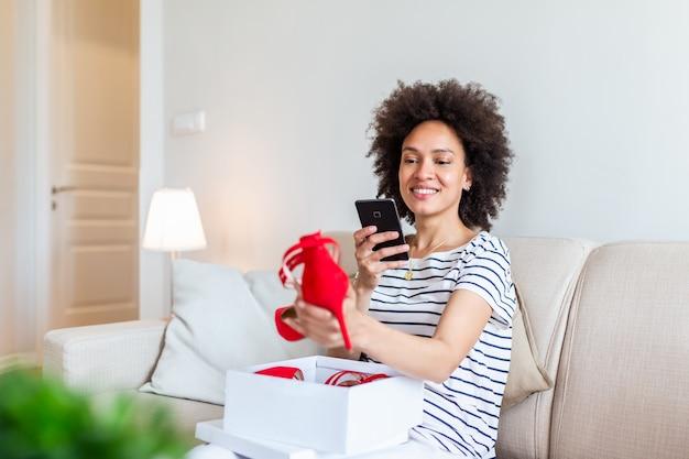 Молодая женщина, сидя на диване у себя дома и лицо, чтобы показать ее новые туфли