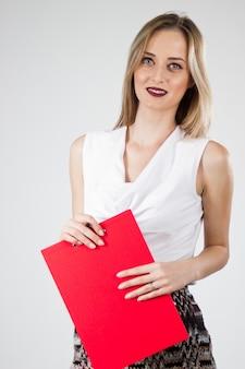 クリップボードと魅力的な近代的な若いビジネスの女性。