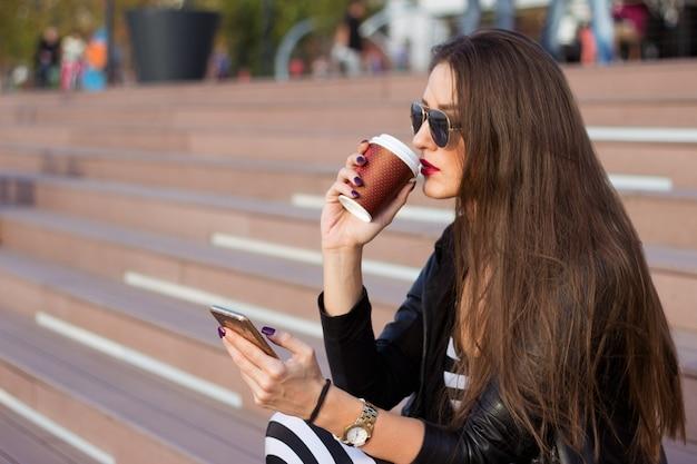 美しい女性は、階段に座って、携帯電話を見て。