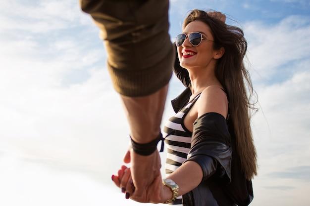 フォローしてください。若い美しい女性は彼女のボーイフレンド、屋外の日没をドラッグします。