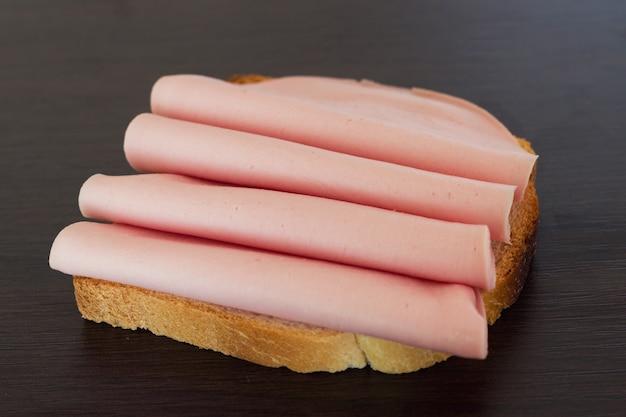 Салями сэндвич. откройте сэндвич с кусочками салями на хлеб.