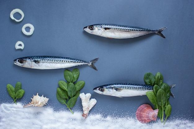 青い背景においしい新鮮な魚。香り高いハーブ、タマネギ、水中の魚の水泳概念