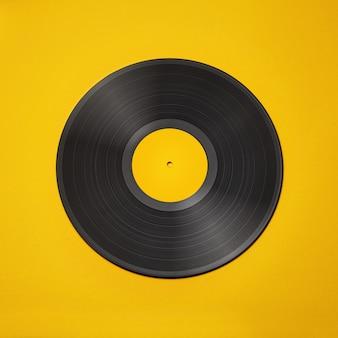 黄色の背景に分離された古いビンテージビニールレコード